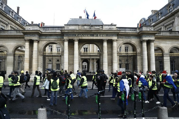 Des gilets jaunes passent devant le Conseil d'État à Paris.